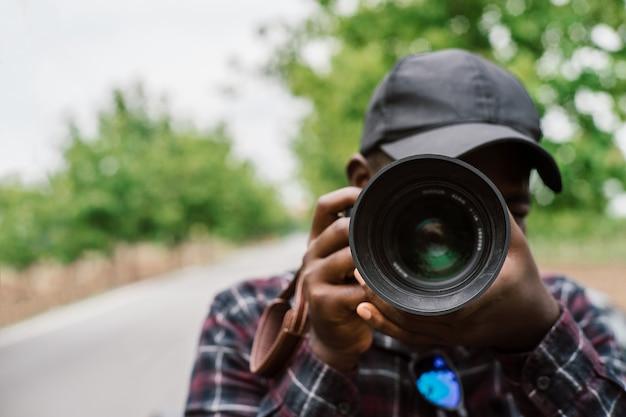 Afrikanischer mann fotograf nimmt eine kamera