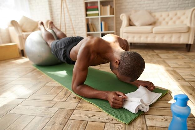 Afrikanischer mann führt planke auf mehl zu hause durch