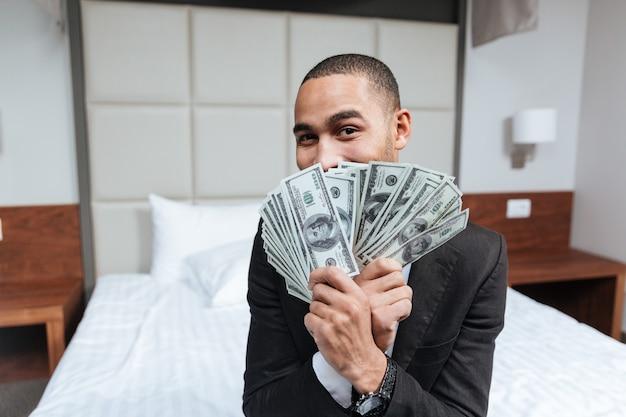 Afrikanischer mann guckt unter dem geld hervor, sitzt auf dem bett im hotelzimmer und schaut in die kamera