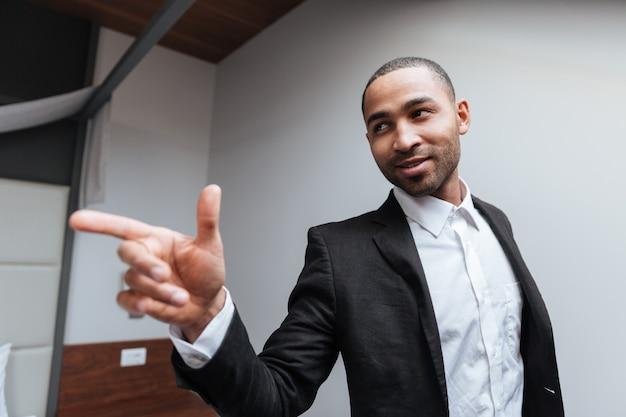 Afrikanischer mann im anzug, der im hotelzimmer weg zeigt