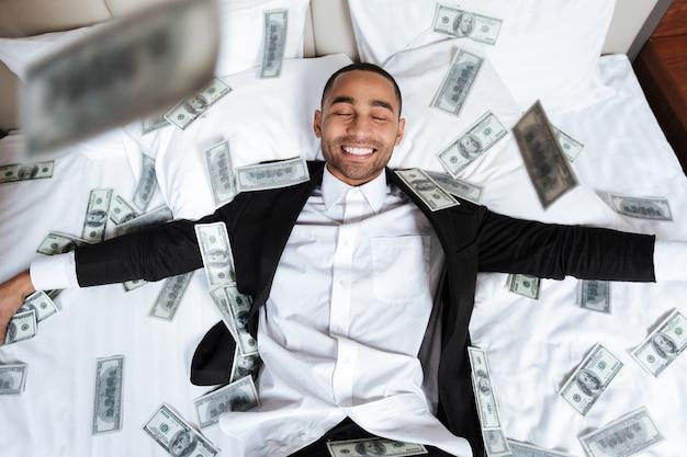 Afrikanischer mann im anzug mit geschlossenen augen, die auf bett im hotelzimmer mit fallendem geld liegen. draufsicht