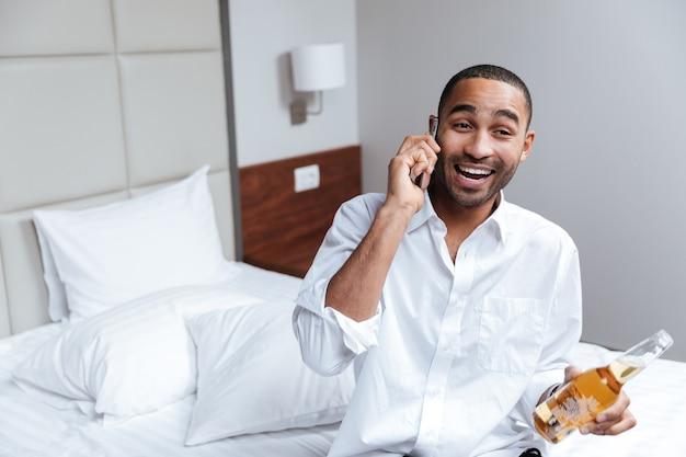 Afrikanischer mann im hemd, der am telefon auf bett mit bier in der hand im hotelzimmer spricht