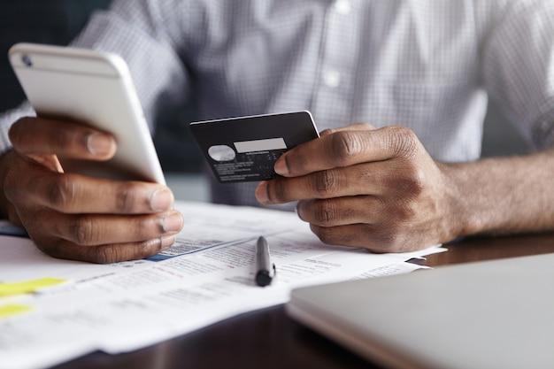 Afrikanischer mann im hemd, der für waren im internet unter verwendung der kreditkarte und des handys zahlt