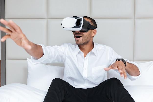 Afrikanischer mann im hemd unter verwendung des virtuellen realitätsgeräts, das auf bett im hotel sitzt