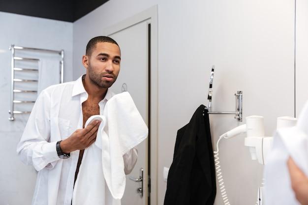 Afrikanischer mann im hemd wäscht im badezimmer im hotel