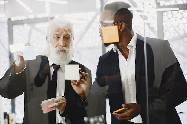 Afrikanischer mann im schwarzen anzug. internationale partner. junger mann mit älterem mann.
