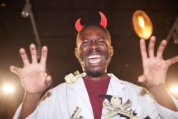 Afrikanischer mann im teufelskostüm an halloween