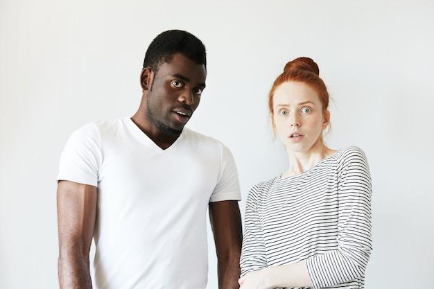Afrikanischer mann im weißen t-shirt und rothaarige kaukasische frau im gestreiften oberteil