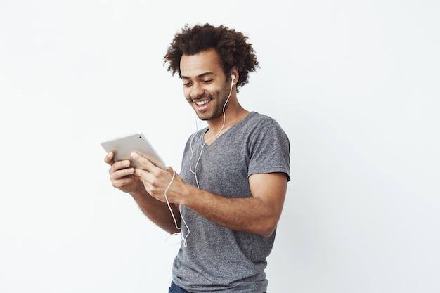 Afrikanischer mann in den kopfhörern, die lachen, tablet halten, sprechen oder sehen und eine comedy-show oder das stöbern genießen.