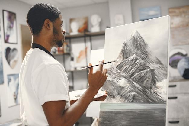 Afrikanischer mann in der malklasse, die auf einer staffelei zeichnet.