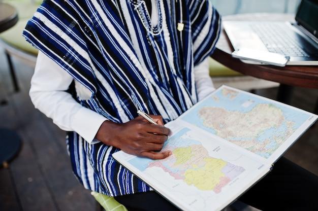 Afrikanischer mann in der traditionellen kleidung, die hinter laptop am außenkaffee sitzt und auf karte von afrika und ghana an seinem notizbuch schaut