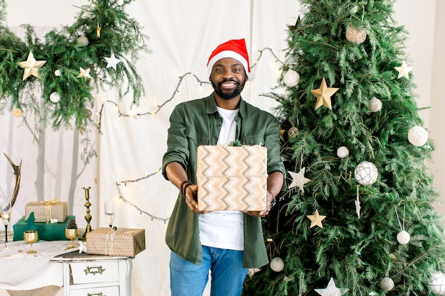 Afrikanischer mann in der weihnachtsmütze mit geschenkbox auf dem hintergrund des weihnachtsbaumes