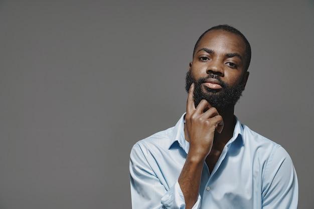 Afrikanischer mann in einem studio. weiße wand. mann in einem blauen hemd.
