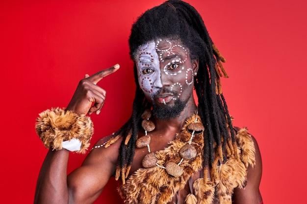 Afrikanischer mann in ethnischer kleidung, der finger am kopf salbt, steht unter schock und redet etwas, isoliert über roter wand