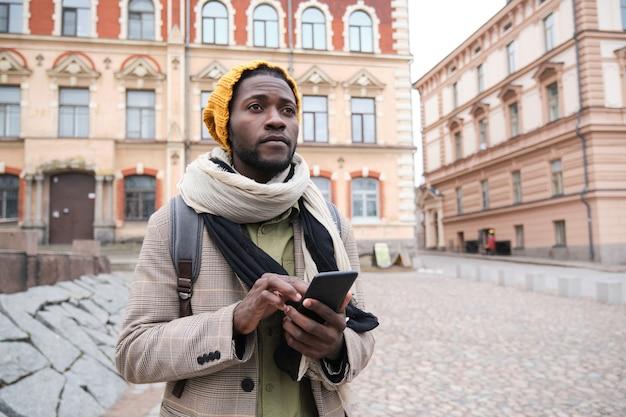 Afrikanischer mann in warmer kleidung mit handy beim stehen in der stadt