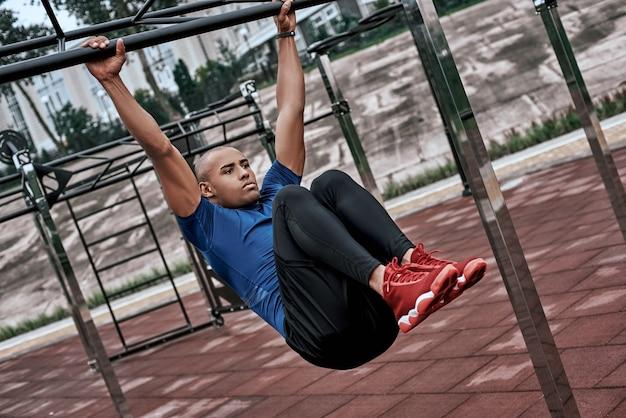 Afrikanischer mann macht dehnübungen im open-air-fitnessstudio in der nähe des parks