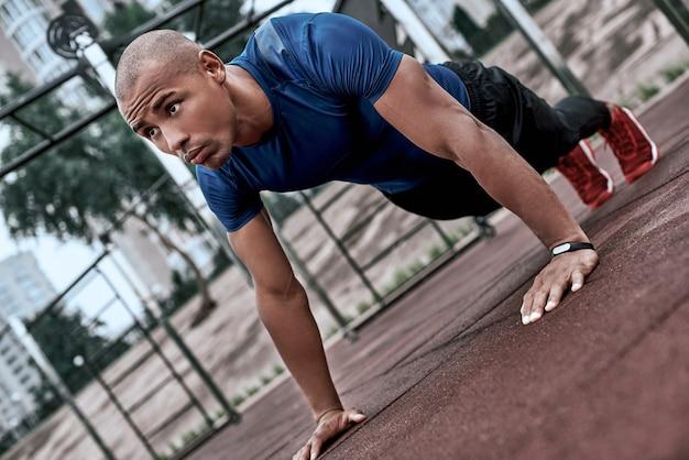 Afrikanischer mann macht plank im open-air-fitnessstudio in der nähe des parks