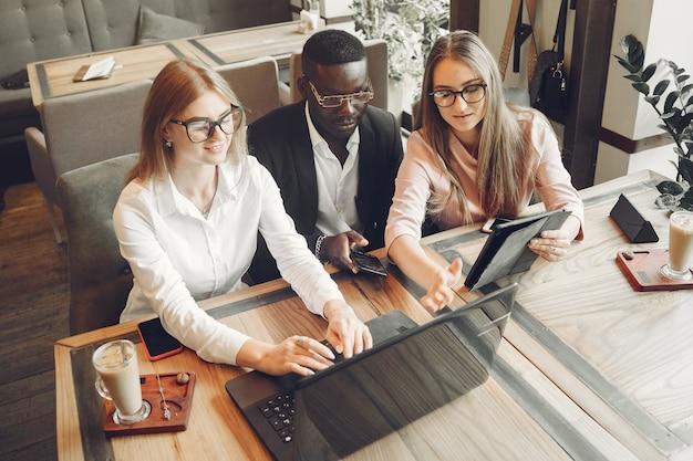Afrikanischer mann. mann in einem schwarzen anzug. studenten mit einem laptop. mädchen in der weißen bluse.