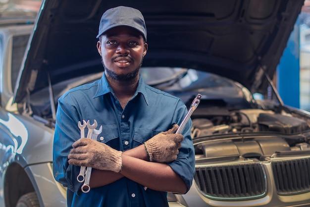 Afrikanischer mann mechaniker in uniform mit verschränkten armen und schraubenschlüsseln, die an der autoreparaturstation stehen