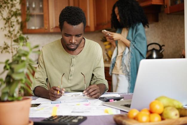 Afrikanischer mann mit brille und bleistift in seinen händen, der frustriert auf papiere vor ihm schaut, während er papierkram erledigt, versucht, alle familienschulden zu bezahlen, mit laptop und taschenrechner am tisch sitzt