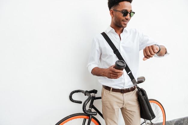 Afrikanischer mann mit dem fahrrad, das kaffee trinkt.