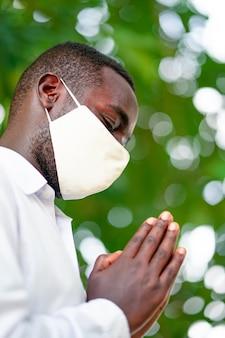 Afrikanischer mann mit gesichtsmaske, der betet, um coronavirus-epidemie zu bekämpfen