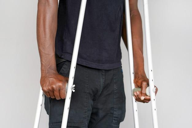 Afrikanischer mann mit krücke. nahansicht. seitenansicht