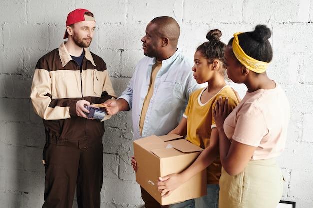 Afrikanischer mann mittleren alters, der für renovierungsmaterialien aus dem online-shop bezahlt, während er die kreditkarte über dem terminal hält, das von einem kurier gehalten wird