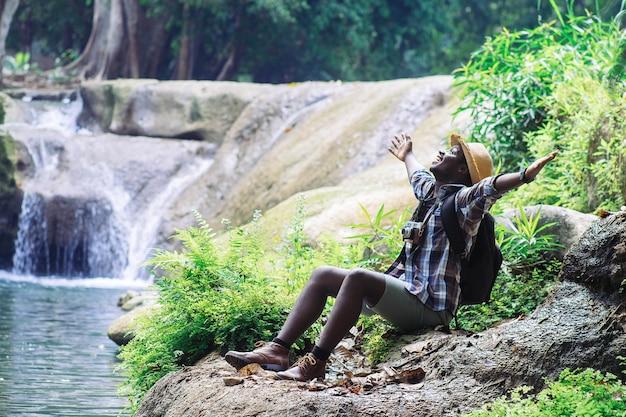 Afrikanischer mann-reisender, der filmkamera hält und freiheit am wasserfall sich entspannt