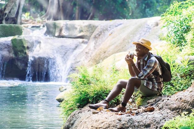 Afrikanischer mann-reisender mit dem halten der filmkamera und der entspannenden freiheit am wasserfall