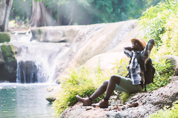 Afrikanischer mann-reisender mit sitzender und entspannender freiheit des rucksacks am wasserfall