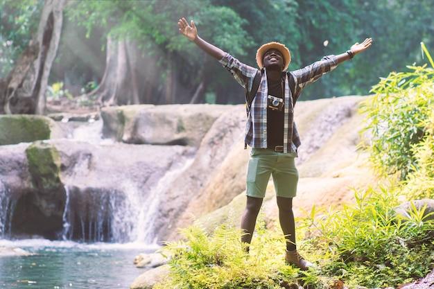 Afrikanischer mann-reisender mit stehender und entspannender freiheit des rucksacks am wasserfall