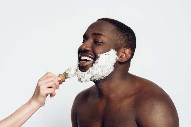 Afrikanischer mann schmiert rasierschaum auf gesicht durch rasierpinsel.