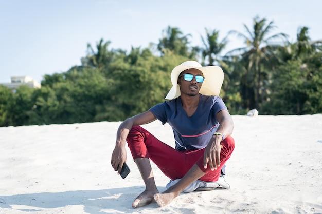Afrikanischer mann sitzt am sandstrand
