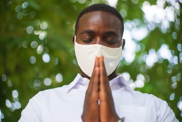 Afrikanischer mann steht und betet zu gott