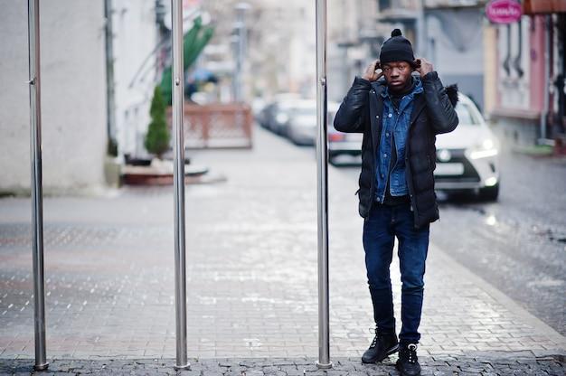 Afrikanischer mann tragen auf jacke und schwarzem hut bei kaltem wetter im freien.