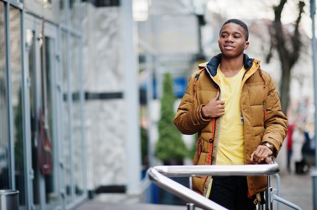Afrikanischer mann tragen auf orange jacke bei kaltem wetter im freien gestellt.