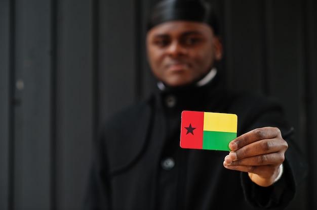 Afrikanischer mann tragen schwarze durag halten guinea-bissau-flagge zur hand isolierte dunkle wand.