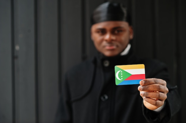 Afrikanischer mann tragen schwarze durag halten komorenflagge zur hand isolierte dunkle wand.