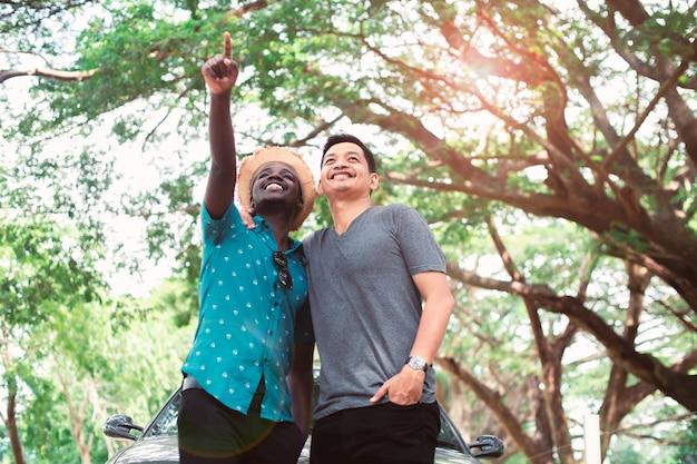 Afrikanischer mann und asiatischer mann, der mit glücklichem, konzept von besten freunden umarmt und schaut