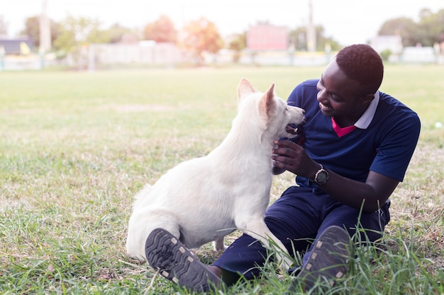 Afrikanischer mann und sein hund, die mit liebe spielt