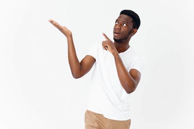Afrikanischer mann zeigt seine hand zur seite auf einem hellen hintergrund kopieren raummodell beschnittene ansicht