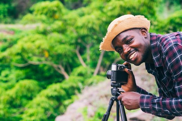 Afrikanischer mannfotograf, der eine filmkamera nimmt