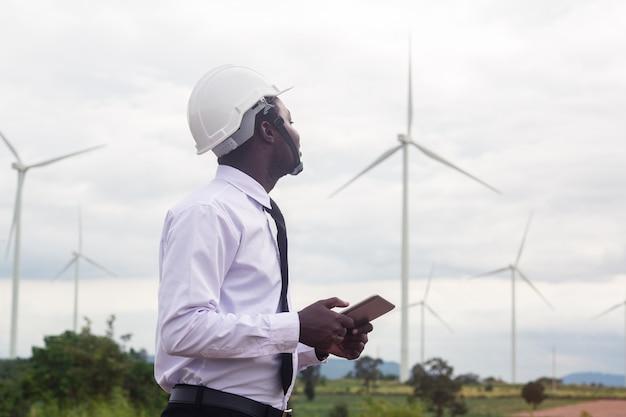 Afrikanischer manningenieur, der laptoptablette mit windkraftanlage hält