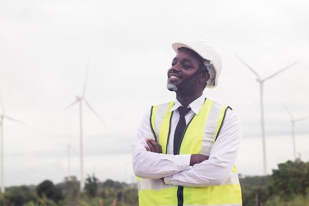 Afrikanischer manningenieur, der mit windkraftanlage steht
