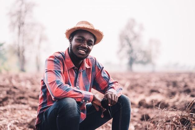 Afrikanischer mannlandwirt, der auf dem feld sitzt.