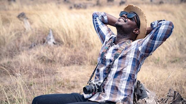 Afrikanischer mannphotograph, der auf dem trockenen gebiet reist.