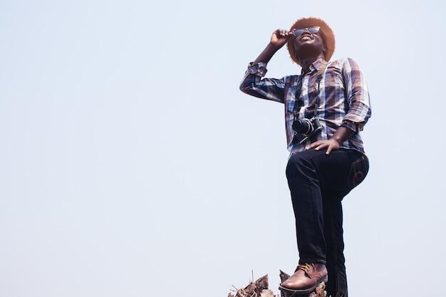 Afrikanischer mannphotograph stehende holdingsonnenbrille und filmkamera auf dem trockenen baum.