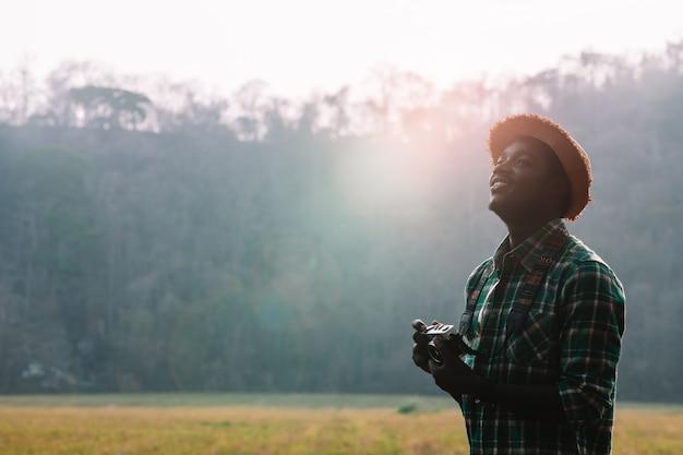 Afrikanischer mannreisender, der filmkamera mit einer grünen wiese und einem berg hält