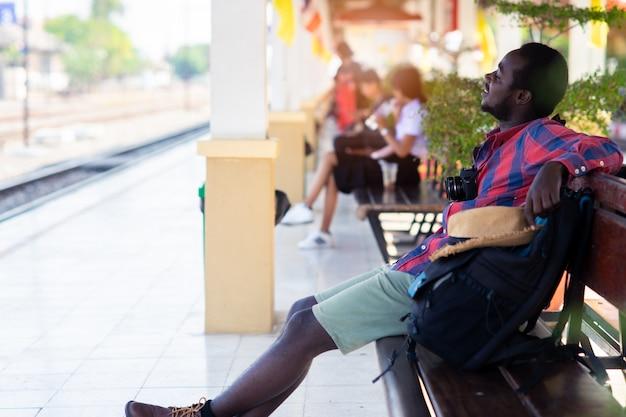 Afrikanischer mannreisender, der mit dem smartphone, kamera und taschewartezug an der bahnstation sitzt
